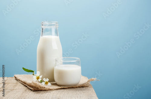 Obraz na plátne  A bottle of milk and glass of milk on a wooden table on a blue background