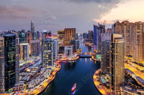 Spectacular view of a big modern city at night. Dubai Marina creek with skyscrapers. Scenic nighttime skyline. Popular travel destination.