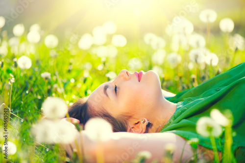 Obraz Beautiful young woman lying on the field in green grass and dandelions - fototapety do salonu