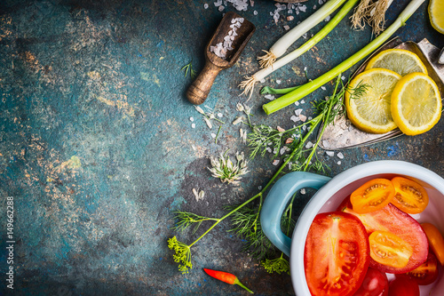 Healthy vegetarian eating and cooking with fresh organic vegetables and seasoning ingredients on dark rustic background, top view