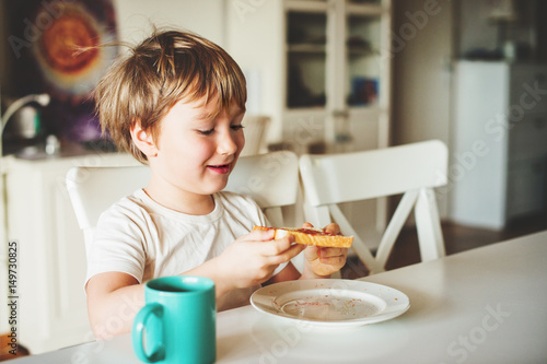 Foto Cute little boy eating his toast with jam and hot chocolate for breakfast