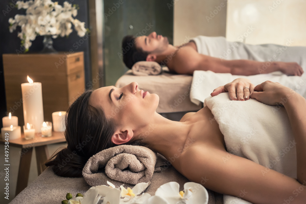 Fototapeta Man and woman lying down on massage beds at Asian wellness center