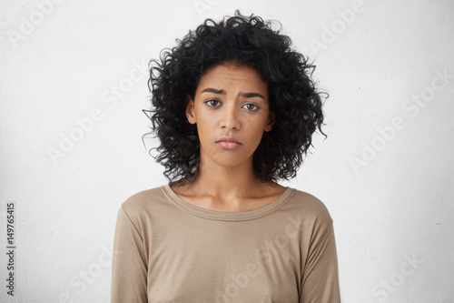 Fotografia Attractive upset young dark skinned lady with Afro hairstyle feeling sad or bored expression while spending weekend at home, looking unhappy after friends forgot to invite her to party