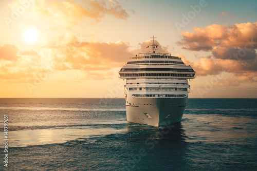 Foto Luxury cruise ship leaving port at sunset