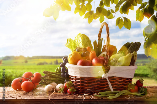 Fruits and vegetables on table and crop landscape background © Davizro Photography