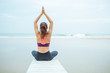 Caucasian woman practicing yoga at seashore on a cloudy day