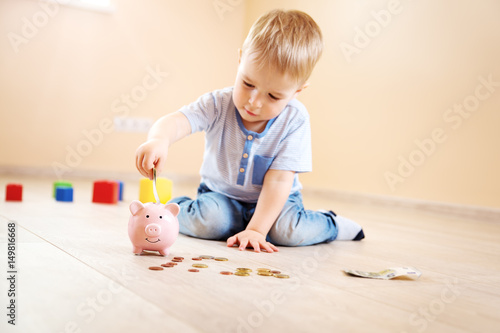 Photo two years old child sitting on the floor and putting money into a piggybank