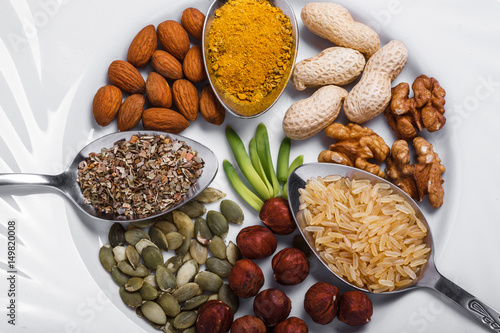 Foto op Canvas Kruiden 2 Assorted nuts in white bowl, plate on wooden surface. peanuts, almonds, hazelnuts, pumpkin seeds, walnuts, rice , buckwheat. Top view with copy space