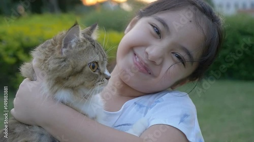 Photo  Slow motion of lovely Asian girl plays with her Persian cat in the park