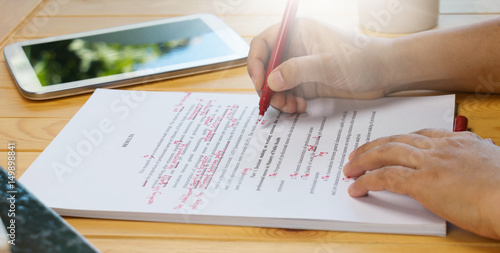 Obraz hand holding red pen over proofreading text - fototapety do salonu