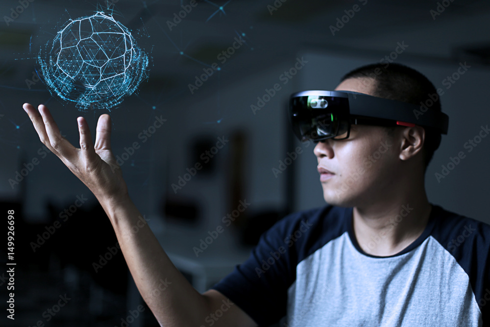 Fototapeta Trying Virtual Reality with hololens glasses.  Business man try virtual reality glasses in the dark room with advanced technology. Future technology concept.