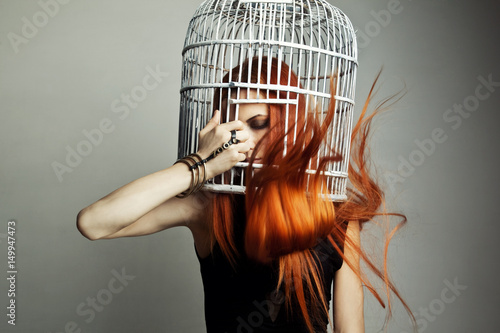 Photo  Beautiful redhead woman with birdcage