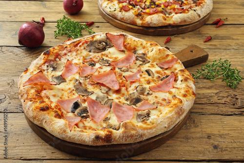 Fotomural pizza con prosciutto e funghi sfondo tavolo rustico