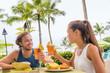 Leinwandbild Motiv Couple eating at hotel restaurant on Hawaii travel vacation beach drinking hawaiian drink mai tai. Happy people toasting cheers with cocktails. Summer holidays at resort.