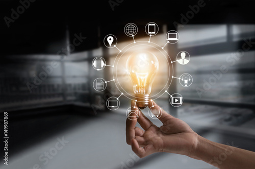 Photo Hand holding light bulb with icons multimedia and customer network connection on