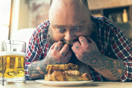 Fat man staring at meat with appetite Poster