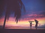Sylwetka surferów ludzie niesie ich surfboard na zmierzch plaży - 150007873