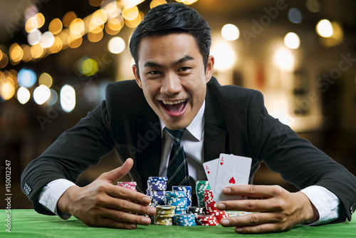 Fotomural The poker gambler showing a pair of red aces and hold bet a large stack with arm