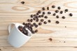 coffee beans from the white ceramic cup on wooden background
