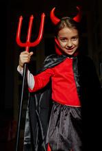 Portrait Of Girl Dressed Up As A Devil Holding A Devil's Fork