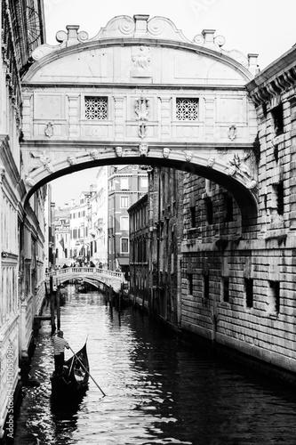 ponte-dei-sospiri-z-plywajaca-w-jego-kierunku-gondola-wenecja-wlochy-czarny-i-bialy