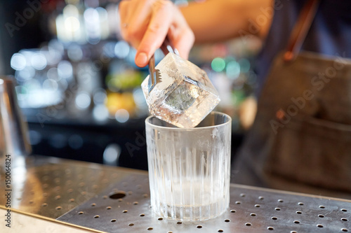 Valokuva  bartender adding ice cube into glass at bar