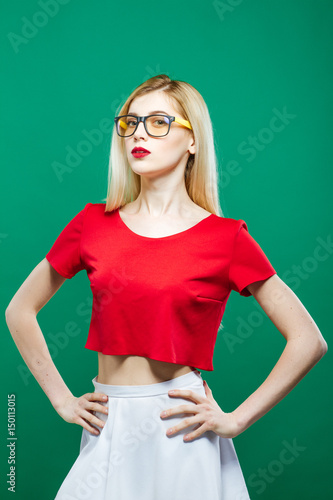 792e3e7317d Young Serious Girl Wearing Short Red Top and Eyeglasses is Posing on Green  Background. Portrait of Sensual Pretty Blonde with Long Hair in Studio.