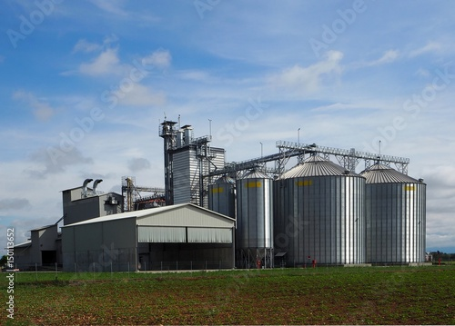 Grain storage bins under blue sky with clouds - Buy this stock photo