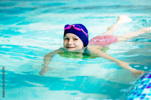 d20c64b1b3 Little girl learning to swim in sport pool. Swimming school for small  children. Healthy