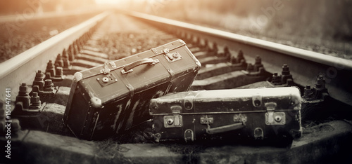 Fotografie, Obraz  Two old fashioned a suitcases on railroad tracks