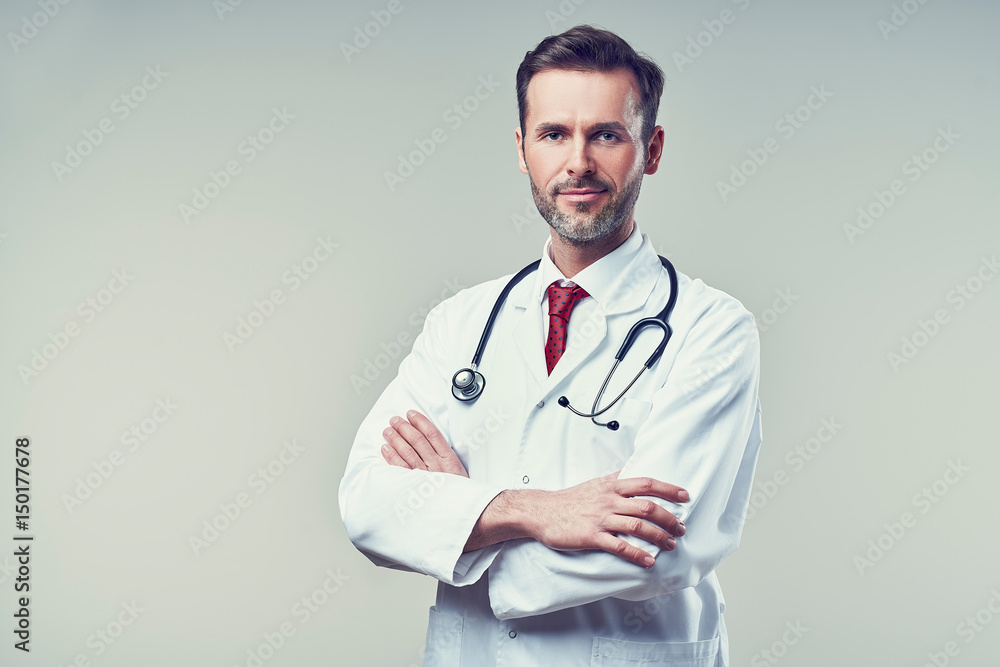 Fototapeta Portrait of handsome doctor standing with crossed arms. Isolated