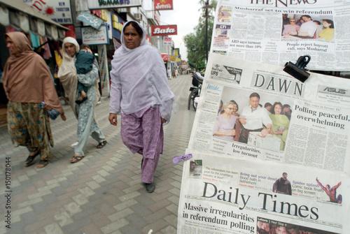 PAKISTANI WOMEN WALK PAST A NEWSPAPER STAND IN ISLAMABAD
