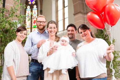 Photo Familie mit Baby nach der Taufe vor dem Altar mit roten Luftballons
