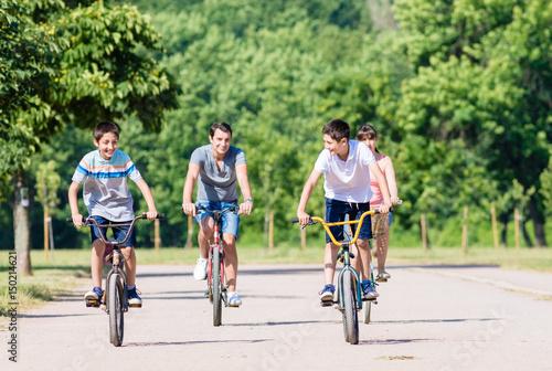 Fotografie, Obraz  Family of four on bike tour in summer