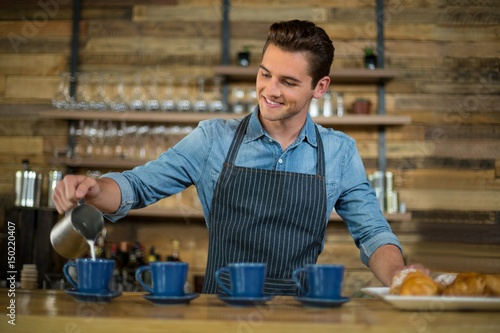 Fotografía  Waiter making cup of coffee at counter