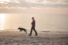Morning Walk Of The Young Man And Black Labrador Dog On The Beach