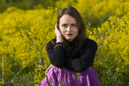 Young woman sitting in a field of yellow flowers Poster