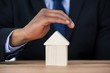 Businessman protecting house model with hands