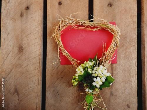 Fotografia Cartão vermelho enquadrado com um coração de palha e ráfia e buquê de pequenos j