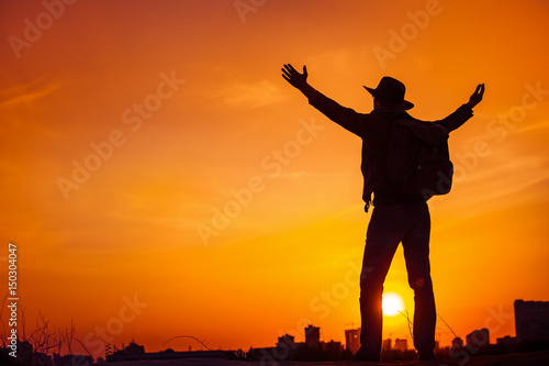 Canvas Prints Military Traveler silhouette of man looking on sunset sky celebrating enjoying freedom, victory, success. Business concept and hands up. Orange toning filter. Lifestyle Travel Outdoor Background. Kiev, Ukraine