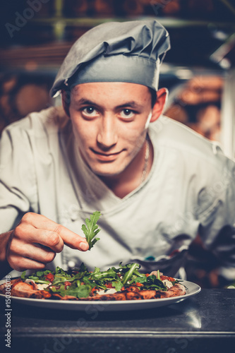 Food concept. Preparing traditional italian pizza. Young handsome chef in white uniform and gray hat decorate ready dish with green rucola herbs in interior of modern restaurant kitchen. Ready to eat. Wall mural