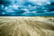 driftender sand im sturm bei dramatischem Himmel
