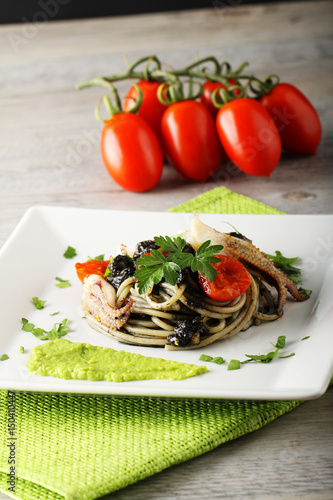 Fotografering  Spaghetti with black sepia, parsley and cherry tomatoes