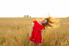 Gorgeous Romantic Girl Outdoors. Beautiful Model In Short Red Dress In Field. Long Hair Blowing In The Wind. Backlit, Warm Color Tones