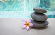 Zen spa stone with plumeria flower over blurred blue swimming pool background