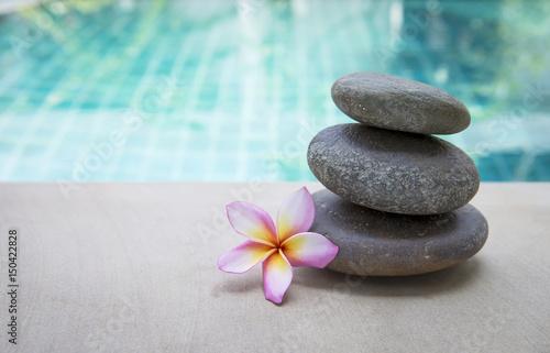 Plakat Zen zdroju kamień z plumeria kwiatem nad zamazanym błękitnym pływackiego basenu tłem