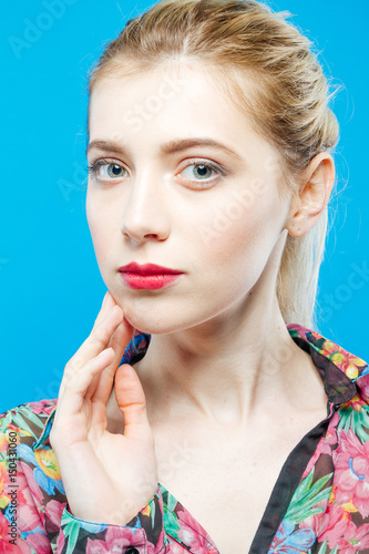 Foto op Plexiglas Beauty Cute Girl with Long Ponytail and Sensual Lips Wearing Colorful Shirt on Blue Background in Studio. Skin Care Concept.