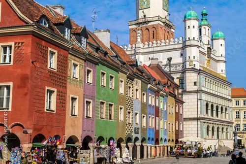 Plakat Niezidentyfikowani ludzie przechodzą obok kolorowych domów Rzemieślników i Ratusza na Starym Rynku, Poznań