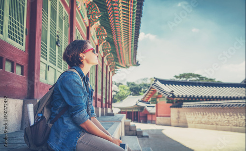 Fotobehang Seoel Woman traveler against the background of historical pagoda buildings in Seoul. Welcome to South Korea