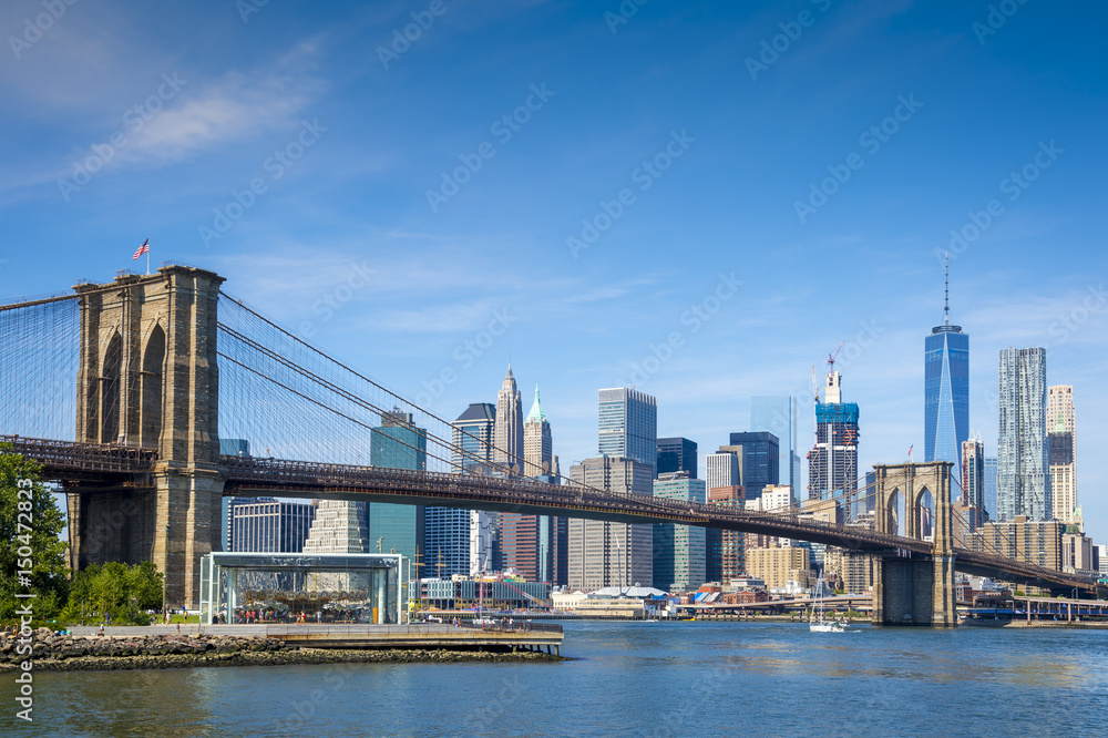 Fototapety, obrazy: Scenic view of Brooklyn Bridge and the Lower Manhattan skyline on a bright day on the East River in New York City